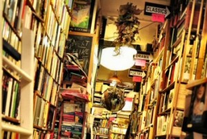 old fashioned bookstore with bookshelves overstuffed, higgly piggly with books