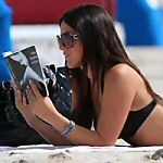 A woman reads E L James 50 Shades of Grey on the beach